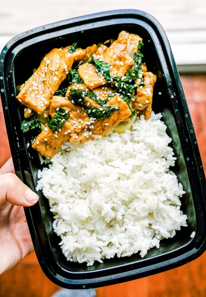 Above view of teriyaki pork in a takeout container