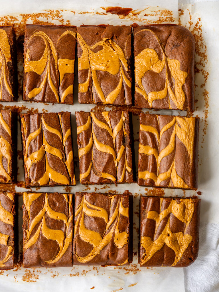 Above view of flourless peanut butter brownies cut into squares on a piece of parchment paper