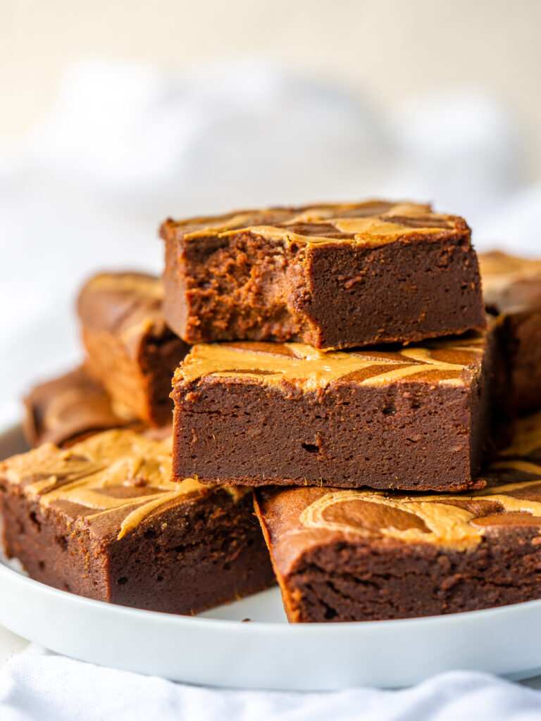 Side view of healthy peanut butter brownies on a serving dish with a bite taken out of one brownie