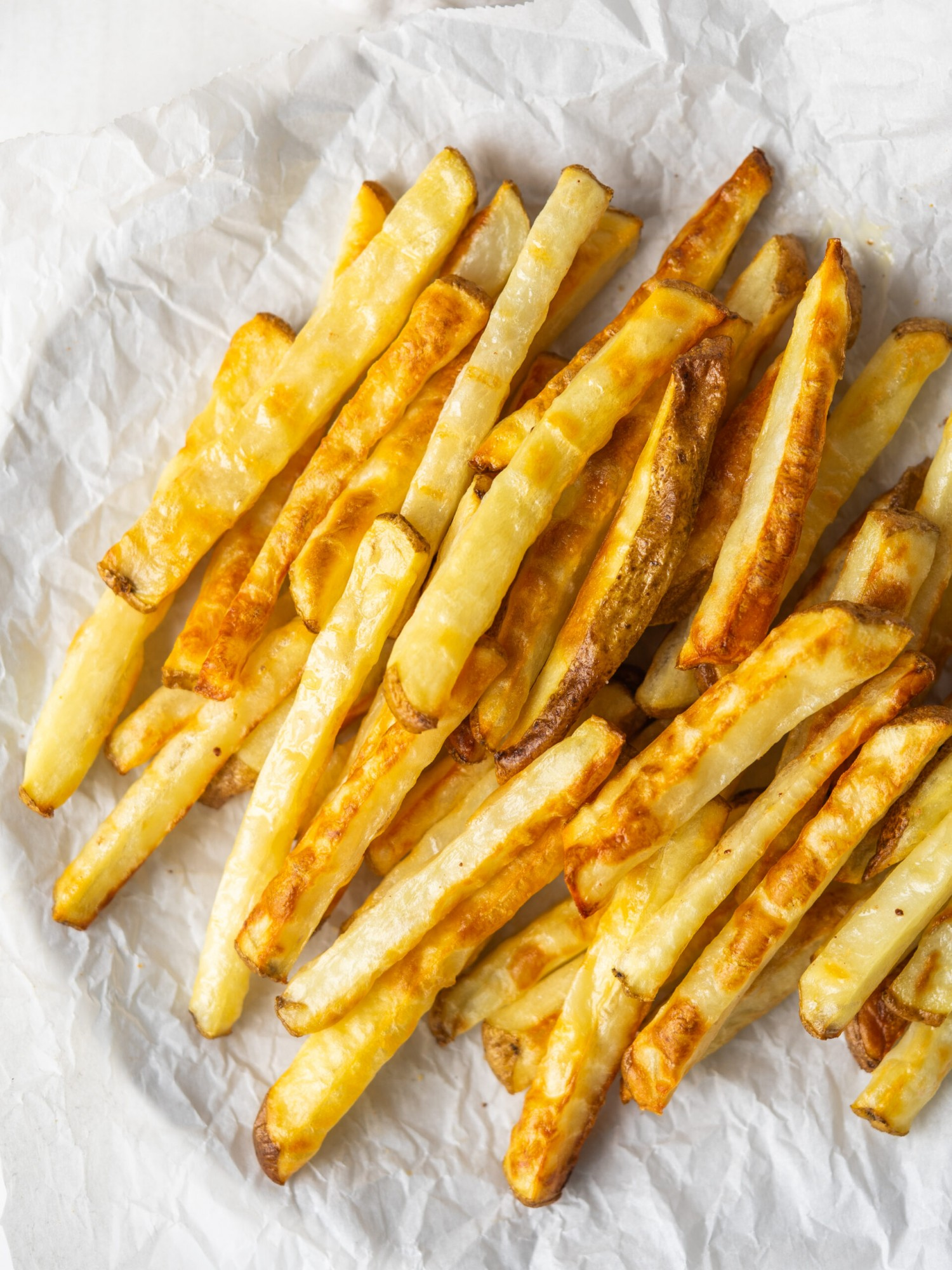 Above view of oven french fries on a piece of parchment paper