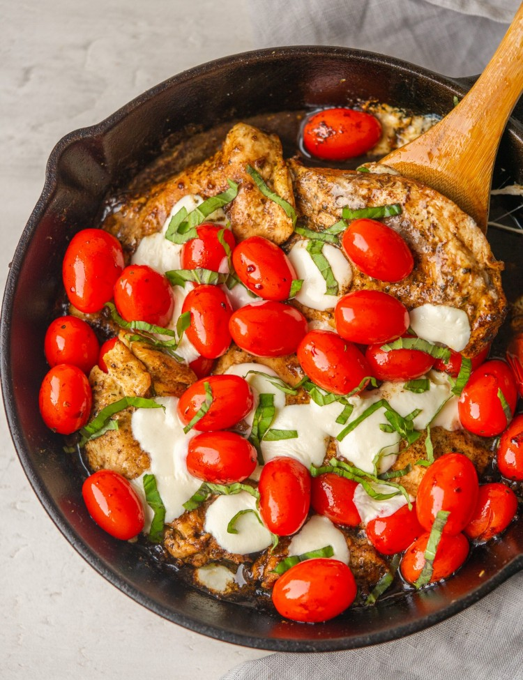 Above view of chicken caprese skillet in a cast iron with a wooden spoon
