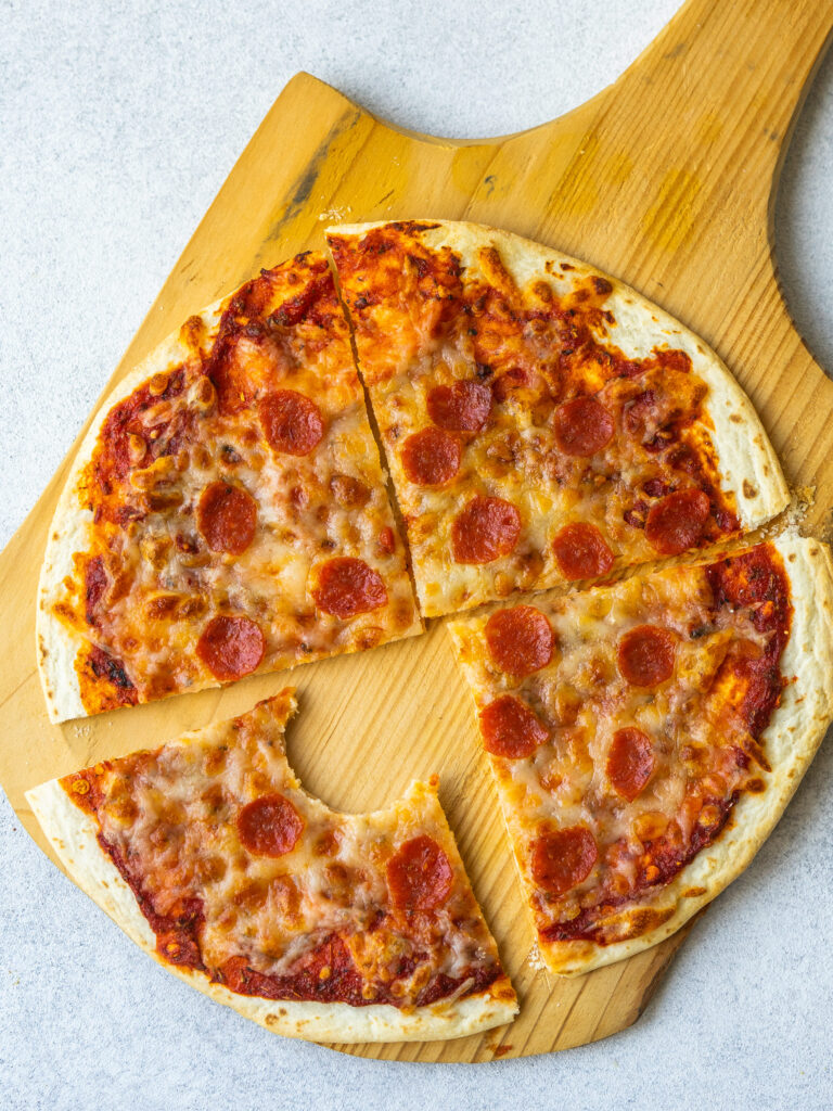 Above view of homemade pizza cut into four slices with a bite out of one slice