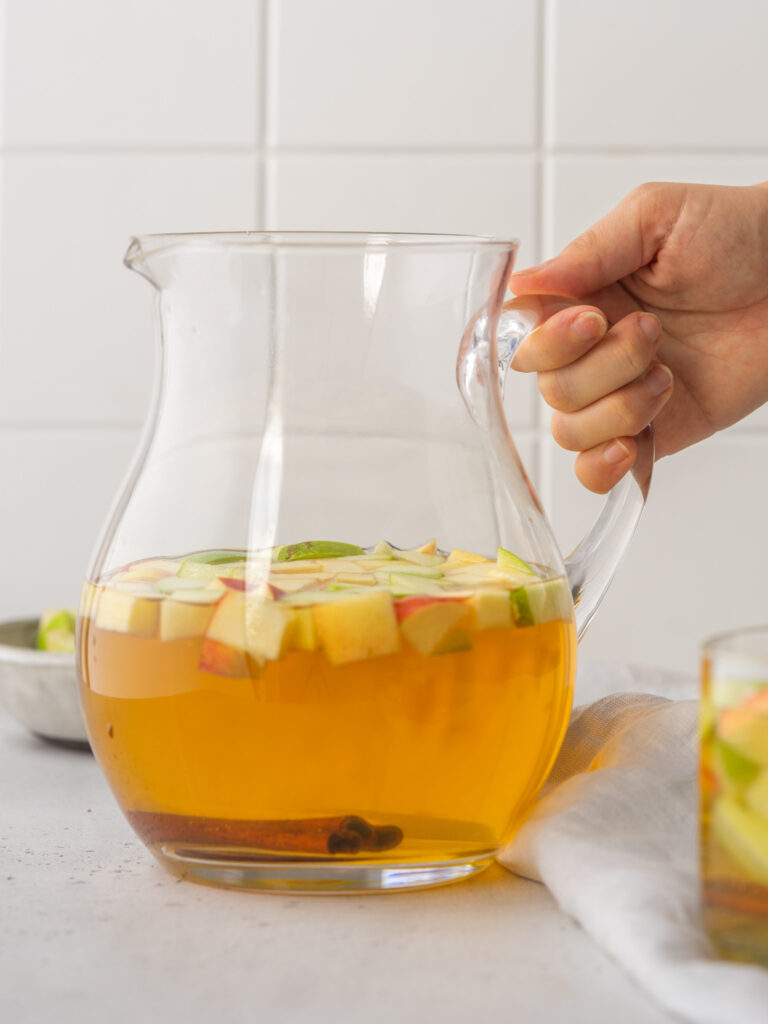 Side view of Apple Cider Sangria recipe in a serving pitcher