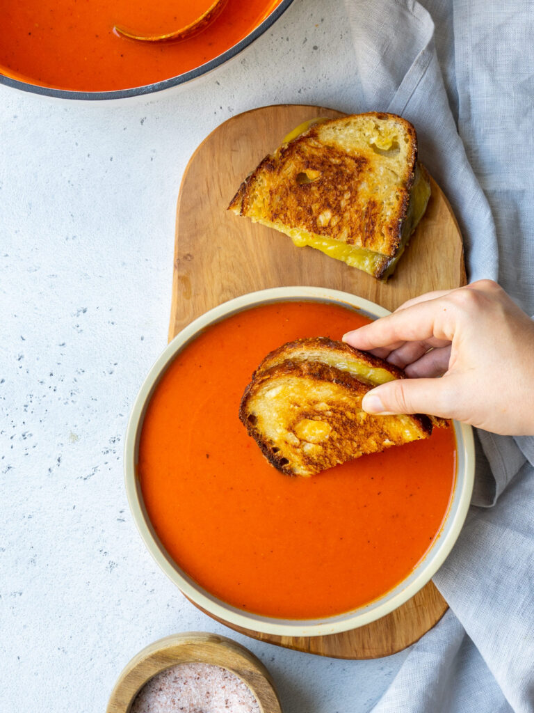 grilled cheese dipping into roasted red pepper soup