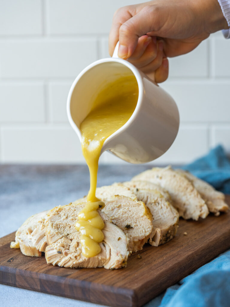 Side view of homemade gravy pouring onto sliced slow cooker turkey breast