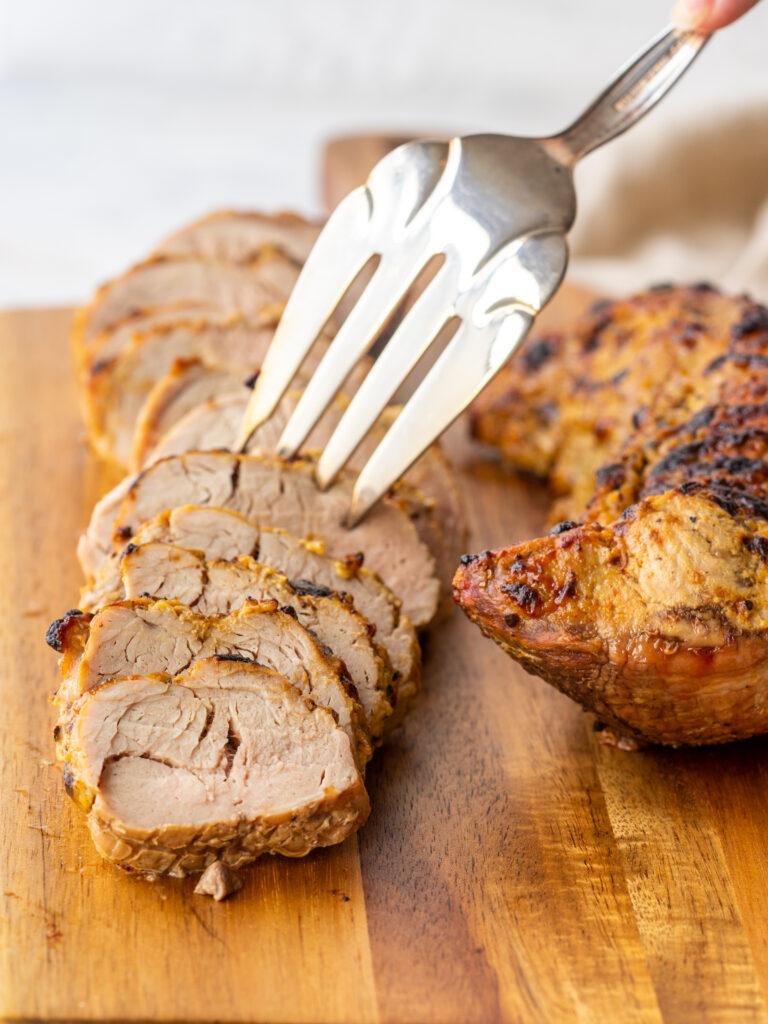 Three quarter view of a fork grabbing a slice of air fryer pork tenderloin