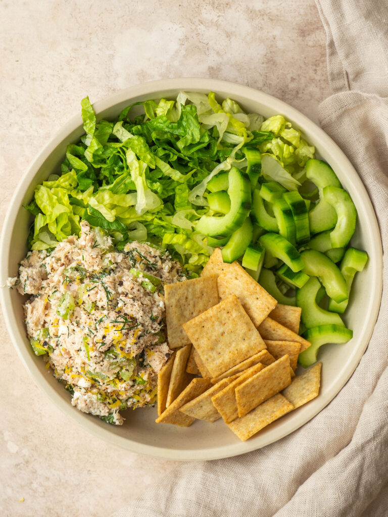 Above view of no mayo tuna salad served on romaine lettuce with crackers and cucumbers