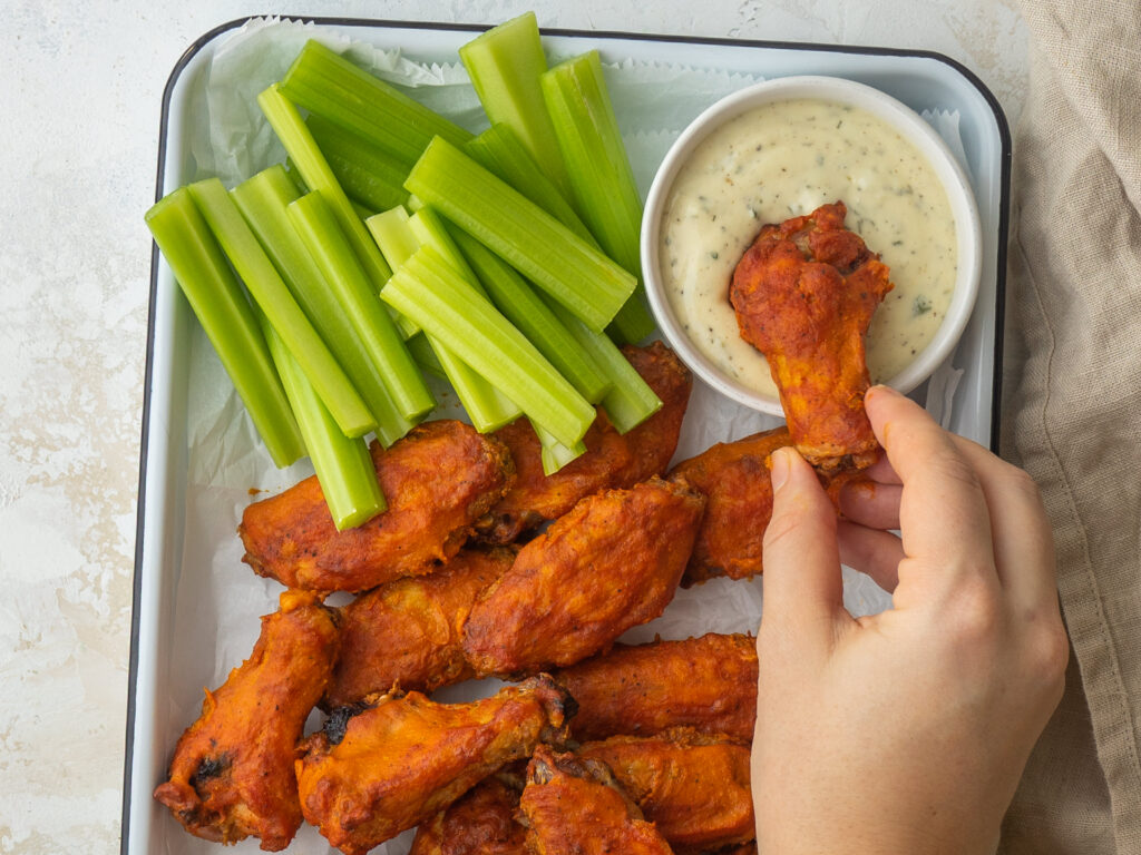 above view of a Carolina gold bbq wing dipping into homemade ranch dressing