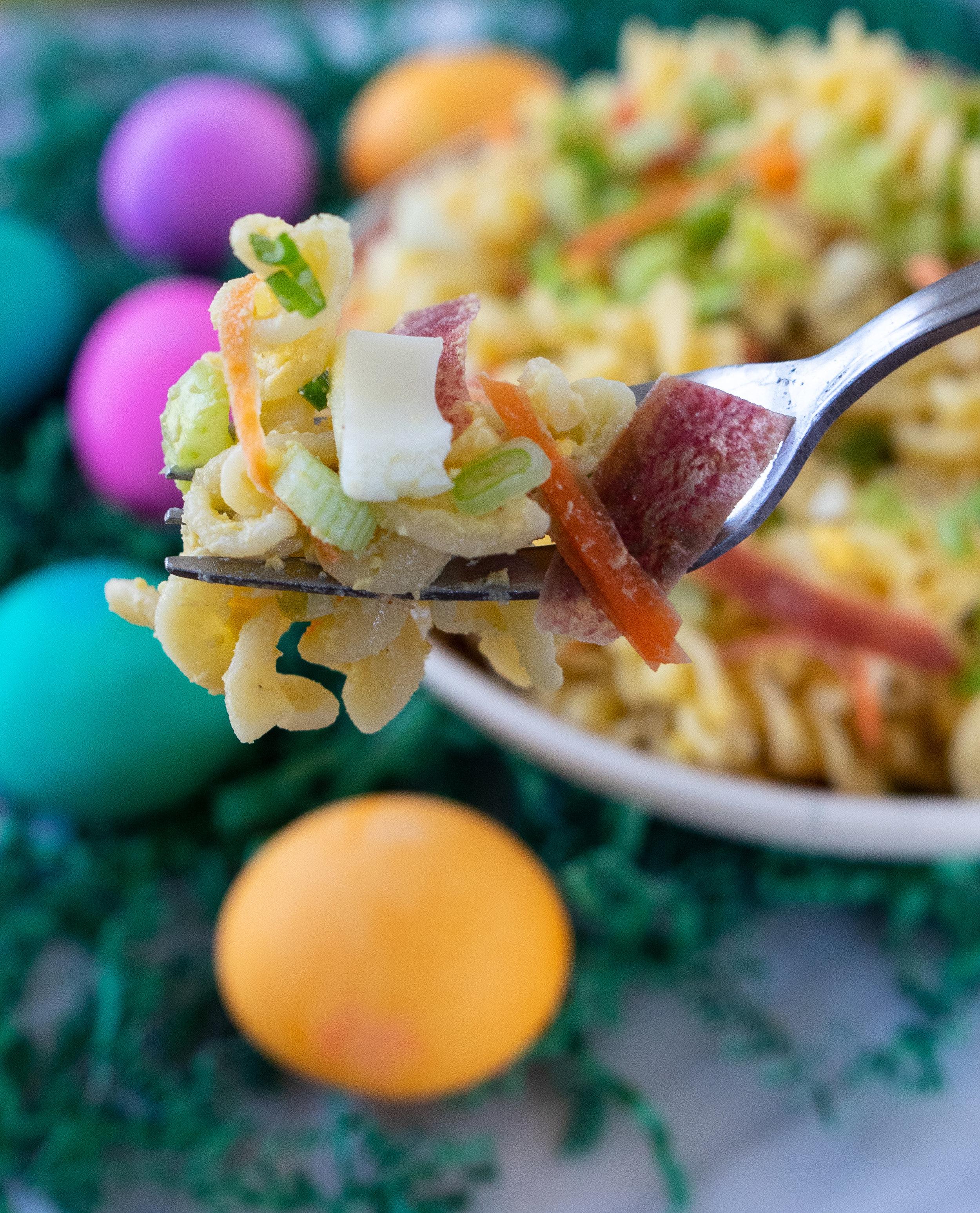 Side view of a forkful of deviled egg pasta salad