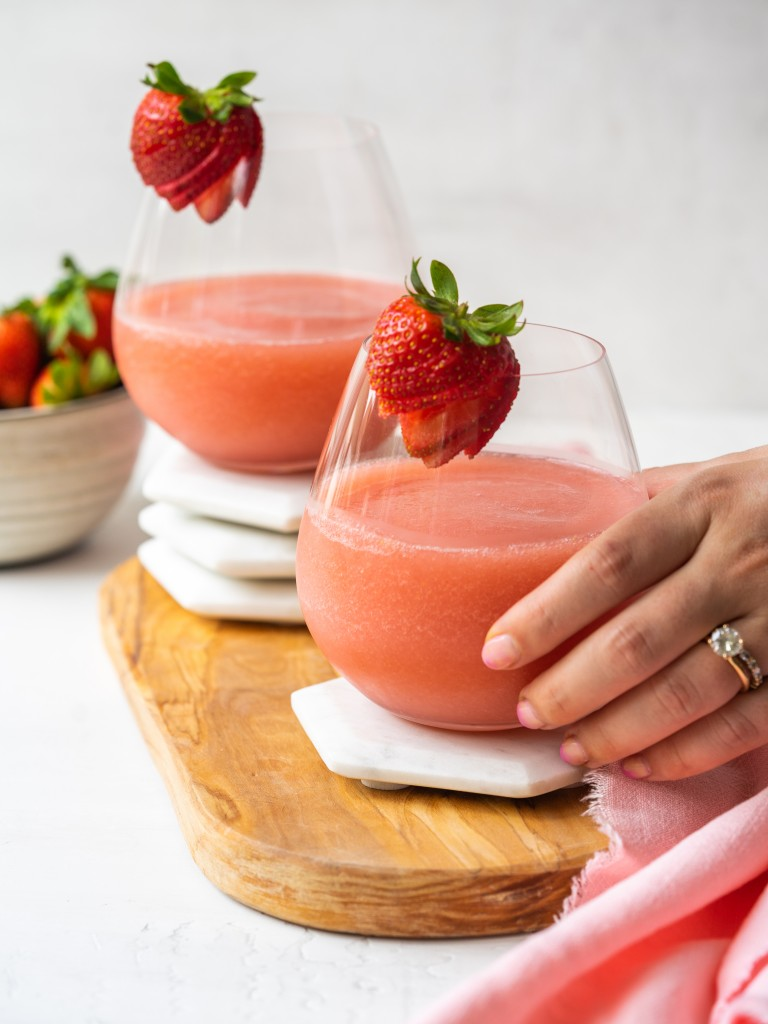 Side view of a hand grabbing a glass of frose