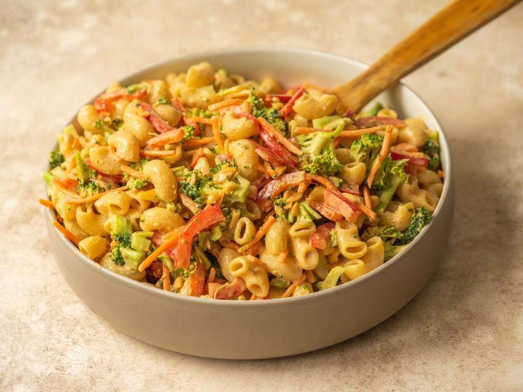 Three quarter view of peanut broccoli pasta salad in a serving bowl