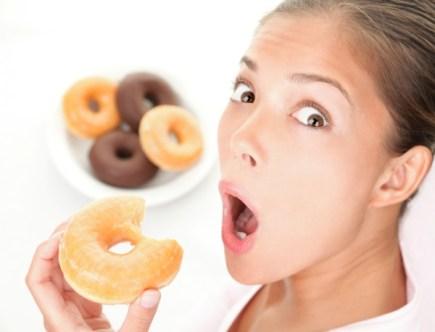 Femme surprise en train de manger un donut