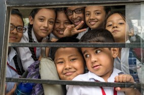 Schoolchildren from the Nightingale School posing on their school bus.