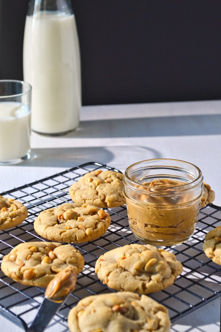 Peanut butter cookies on a black cooling rack beside a jar of peanut butter and a glass of milk in the background