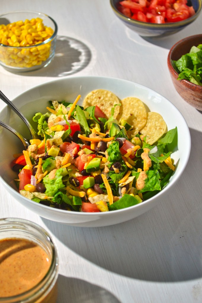 taco salad in a white bowl beside a jar of spicy cashew dressing and separate bowls of corn, tomatoes, and lettuce on a white wooden board