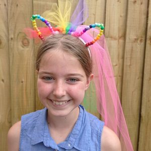 DIY pony craft party - girl wearing a rainbow pony headband with beaded ears and a colourful mane