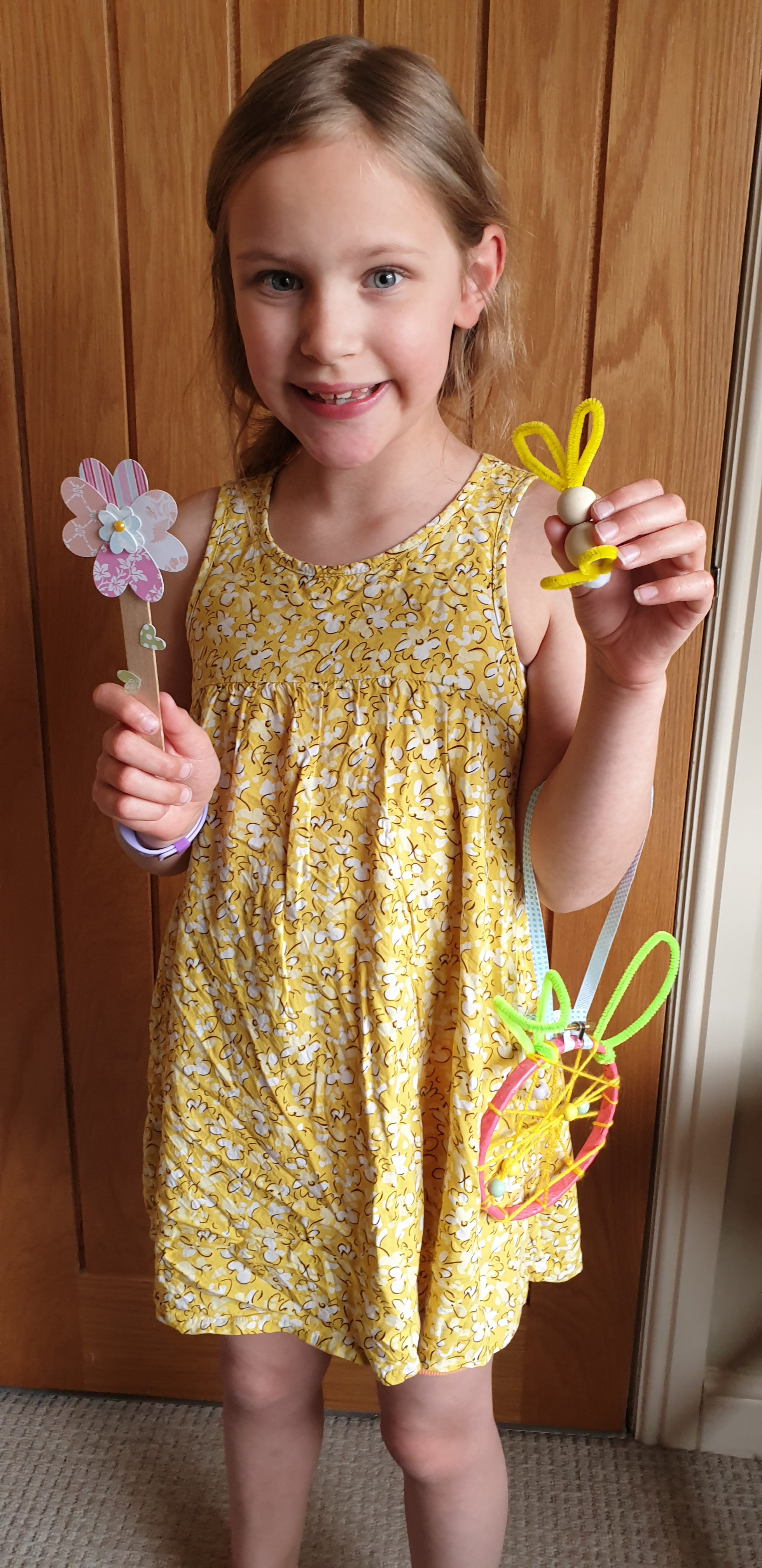 Girl in yellow dress holding Easter dream catcher