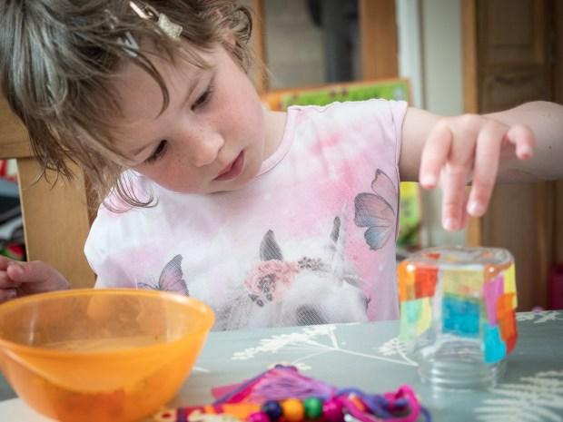 Girl decorating her summer craft kit lantern