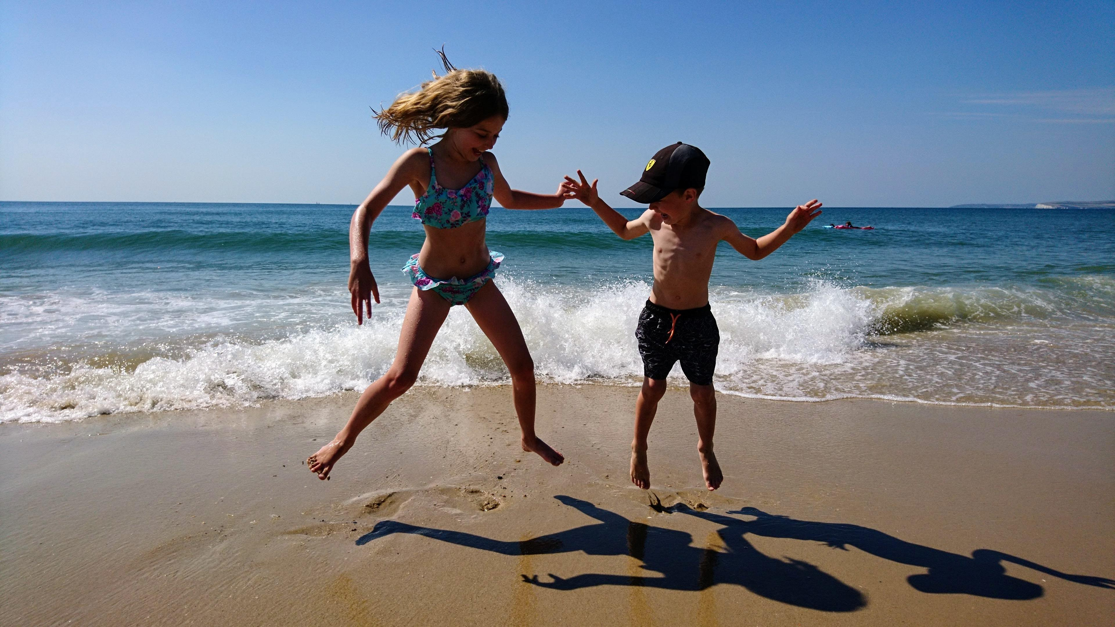 a girl and boy jumping in the air at the beach
