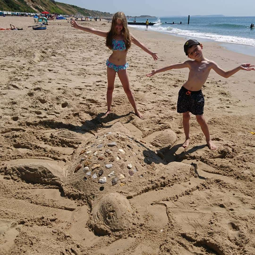 Easy summer crafts for kids. Turtle sculpture made out of sand on the beach with a boy and girl standing by it.