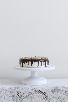 Two layer, 8 inch chocolate cake. With vanilla frosting, chocolate ganache drip, and crushed walnuts.