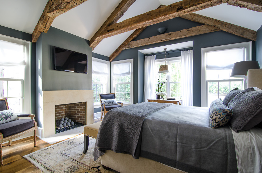Chic Matelasse Bedding In Bedroom Farmhouse With Fireplace Vaulted Ceiling Next To Art Above Tv Alongside Gray Wall White Trim And Beams