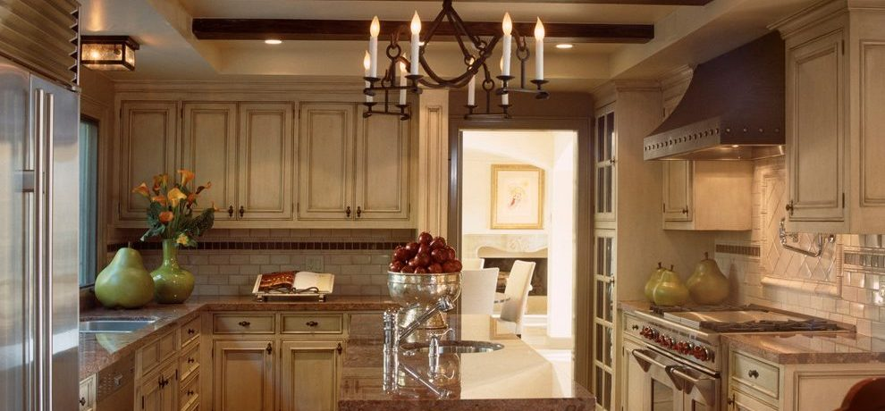 Splendid copper canyon granite Mediterranean Kitchen in Los Angeles with iron chandelier and beige cabinets