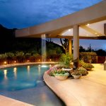 Splendid pondless water feature in with stucco siding and arched pool