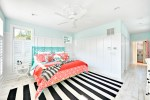 Brilliant Gray and Coral Bedding Bedroom Beach Style with Bold Colors White Painted Wood Floor Plantation Shutters Ceiling Fan Turquoise Bright Patterns Beach Home Blue