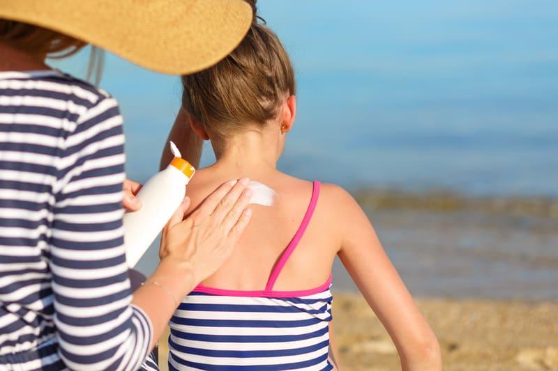 Mom applying the best sunblock for kids on her daughter's back
