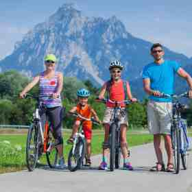 Family taking a bike ride together with picturesque mountains in the background. Discover 4 simple strategies for how to end sibling rivalry for good. And for more parenting tips and family inspiration, follow Made In A Pinch on Pinterest!