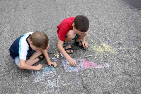 Siblings creating a sidewalk chalk masterpiece together. Discover 4 simple strategies to end sibling rivalry for good. And for more parenting tips and family inspiration, follow Made In A Pinch on Pinterest!
