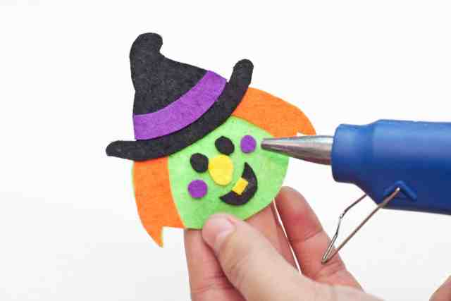 Witch Halloween bookmarks craft for kids tutorial, Gluing on the purple strip for the hat, the eyes, nose, mouth, and dimples