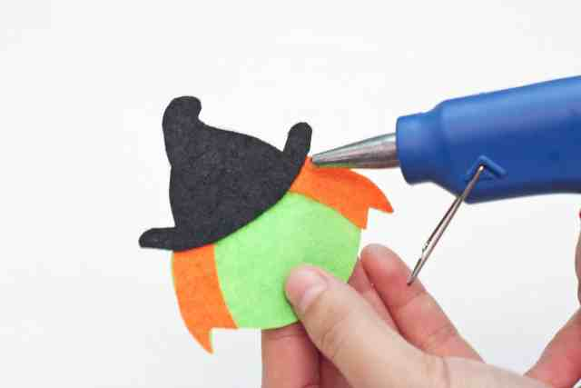 Witch Halloween bookmarks craft for kids tutorial, gluing the hat on top of the witch's head