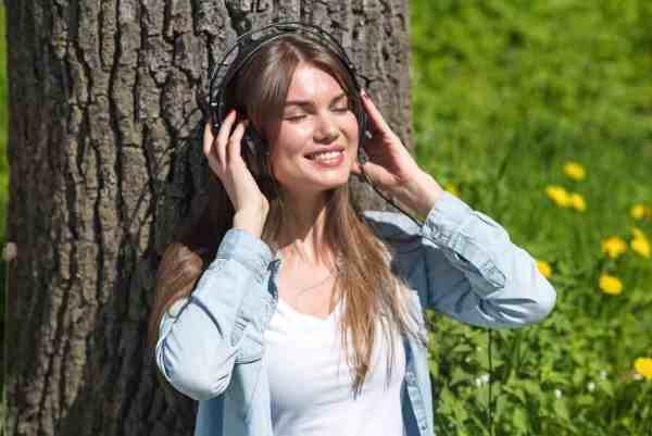 Woman sitting and enjoying music or an audiobook is a great idea for self care gifts for moms