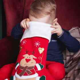 Toddler boy looking into his Christmas stocking for one of the top toddler stocking fillers ideas on this list.