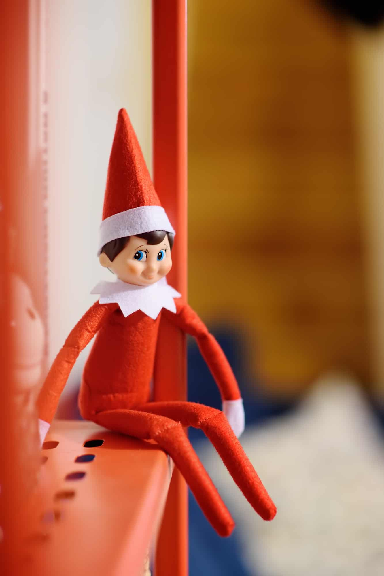 Elf on the shelf sitting on a shelf is part of this mega list of elf on the shelf ideas for toddlers that any busy, tired mom can do