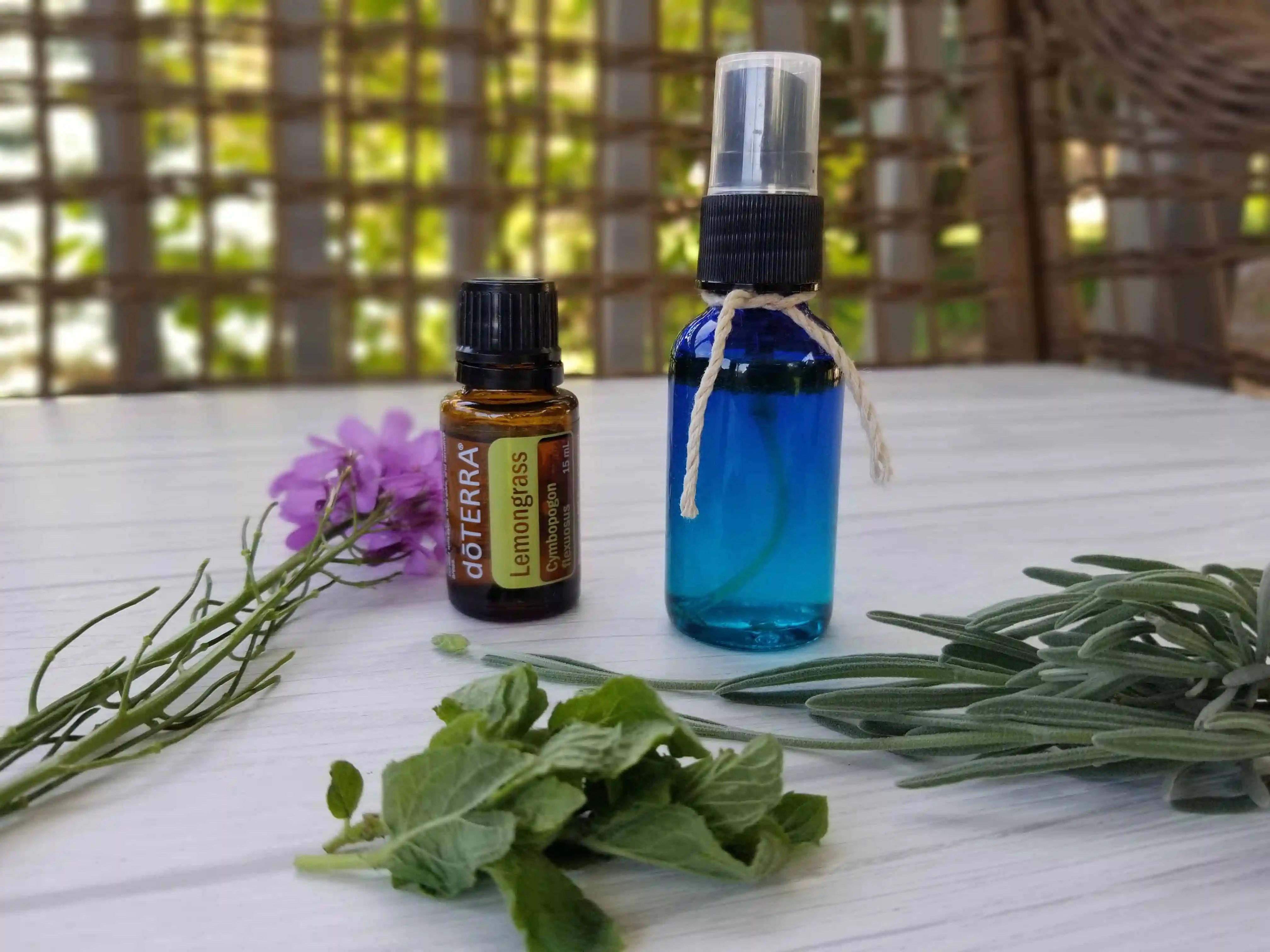 blue spray bottle, lemongrass essential oil bottle and greenery