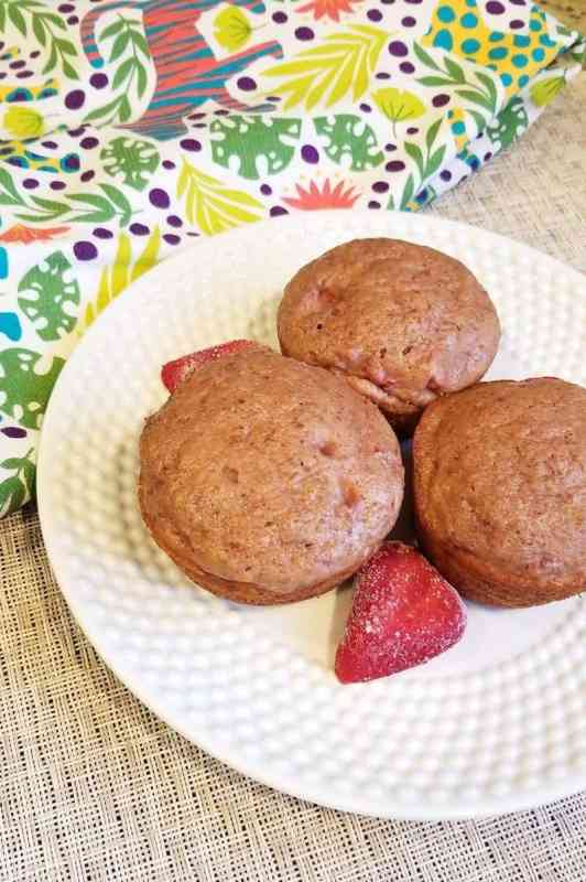 three strawberry muffins on a plan with cut strawberries
