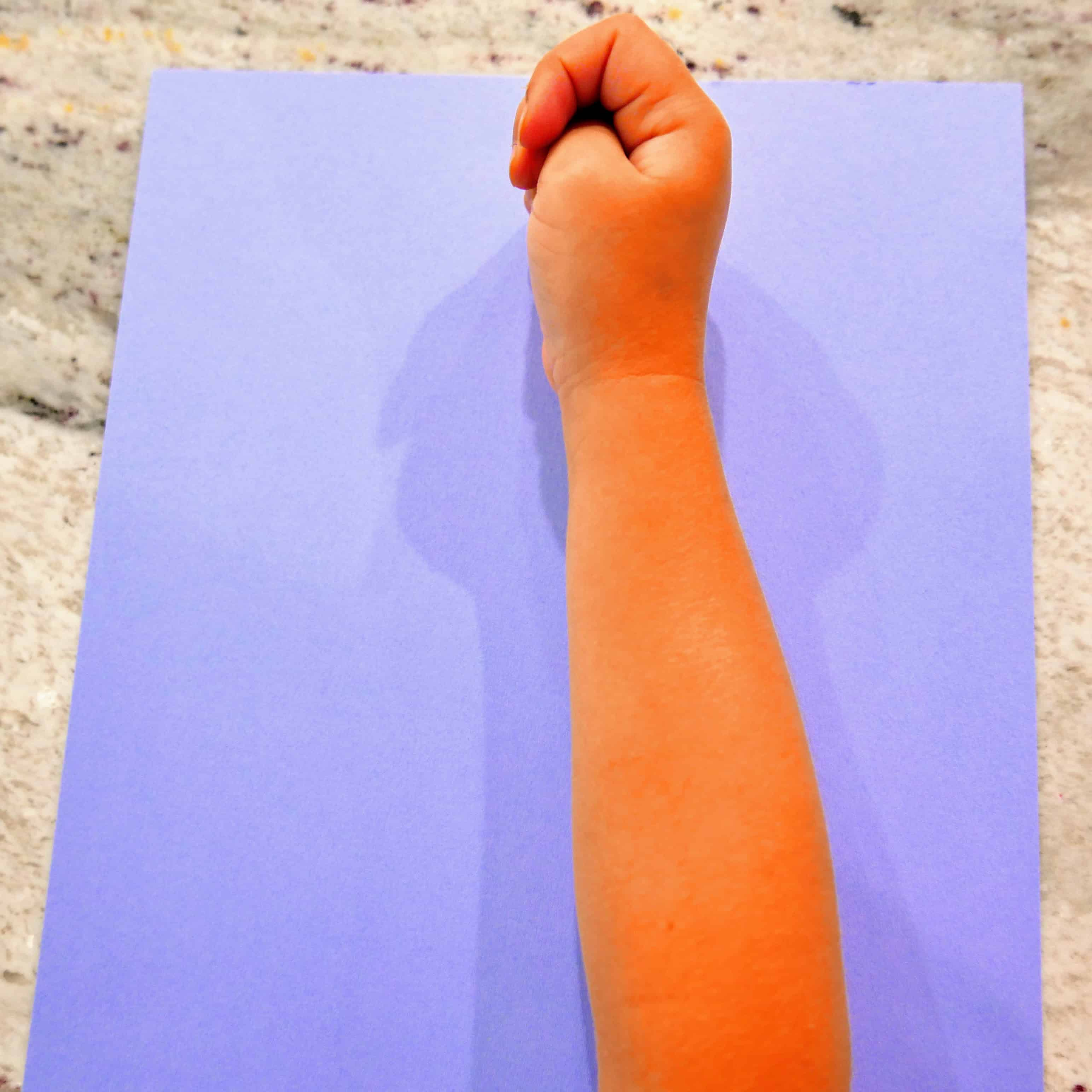 child's arm on top of cardstock paper