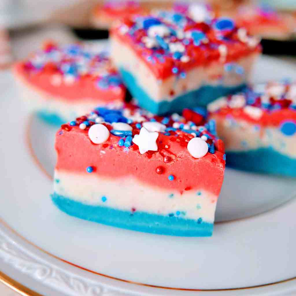 Patriotic red, white, & blue vanilla fudge recipe pieces stacked on a plate