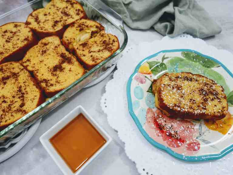 pan of pumpkin french toast with a piece on a plate and a side of maple syrup.