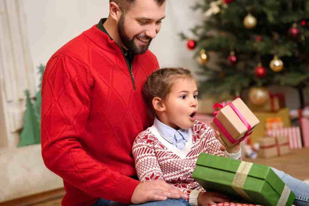 dad sitting with girl as she's opening holiday gifts