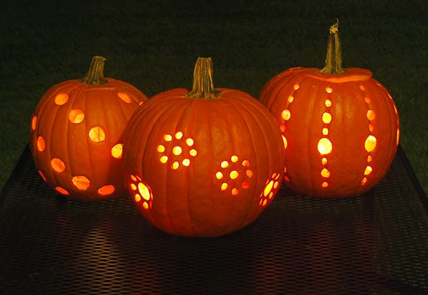 pumpkin decorating ideas for kids includes drilling patterns of holes into pumpkins like these and lighting them up