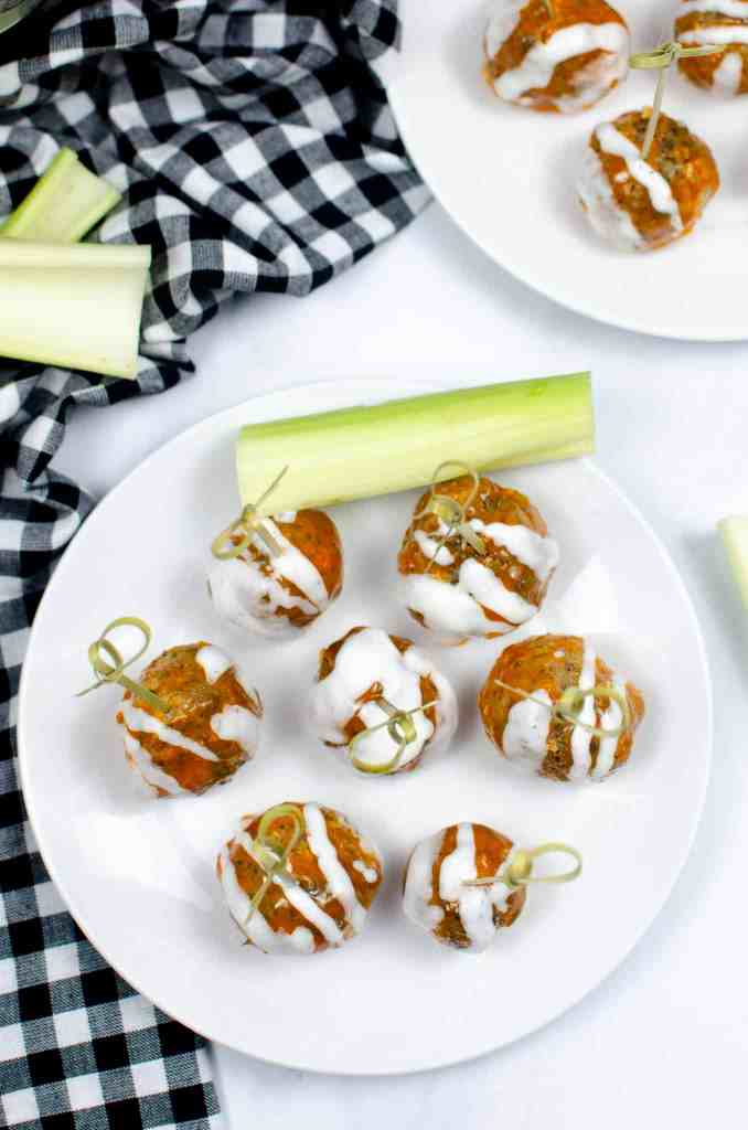 buffalo chicken meatballs on a plate with celery