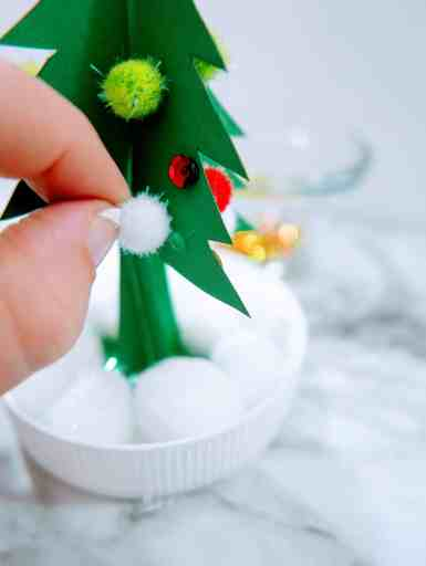 gluing poms and sequins onto the tree for the inside of the homemade snow globe