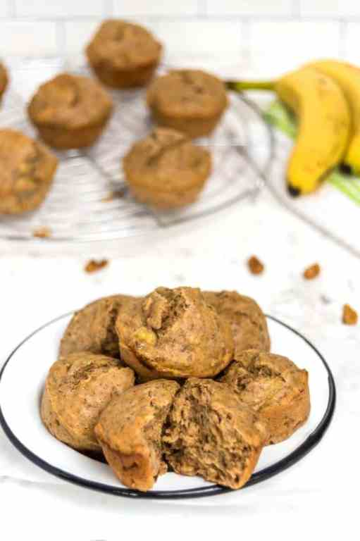 protein banana muffins on a plate with muffins and bananas in the background