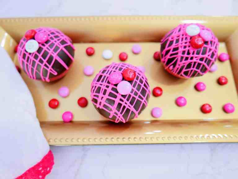 Valentine's M&M hot cocoa bombs on a gold tray