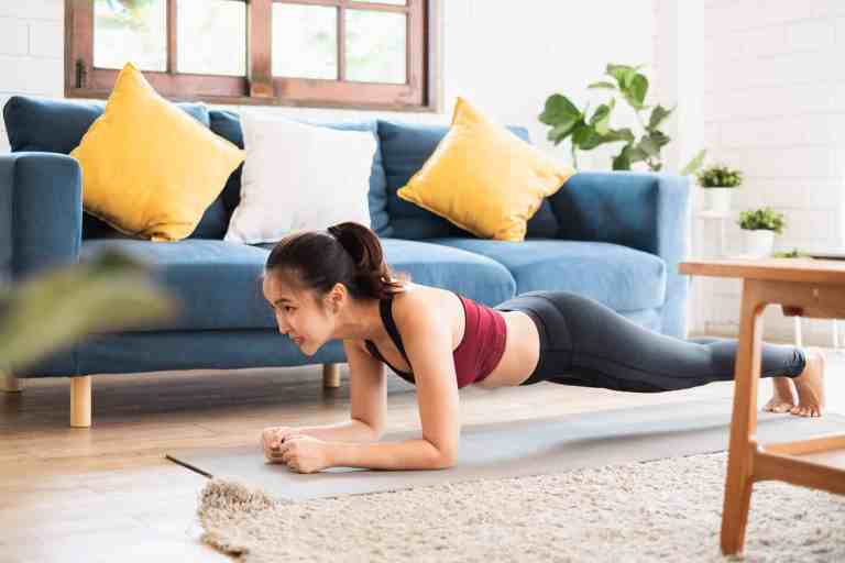 young woman doing a plank in her living room