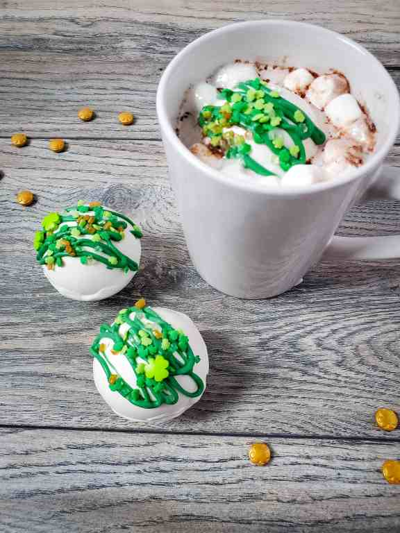 St. Patrick's Day hot cocoa bombs and mug of hot chocolate